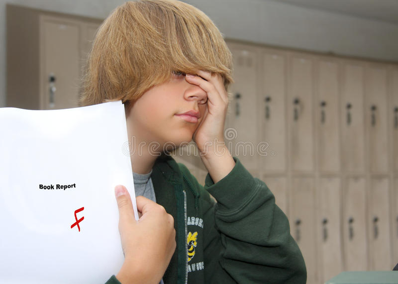 Despair. Young teen boy with expression of despair upon finding a F grade on his paper royalty free stock image