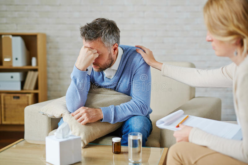 Despair. Ed men with pillow and handkerchief being reassured by his psychologist royalty free stock photography