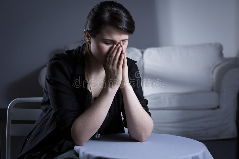 Despair divorced woman. Sitting at the table and crying stock photography