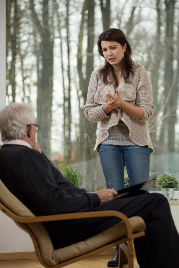 Despair girl talking with psychiatrist. During therapy royalty free stock image
