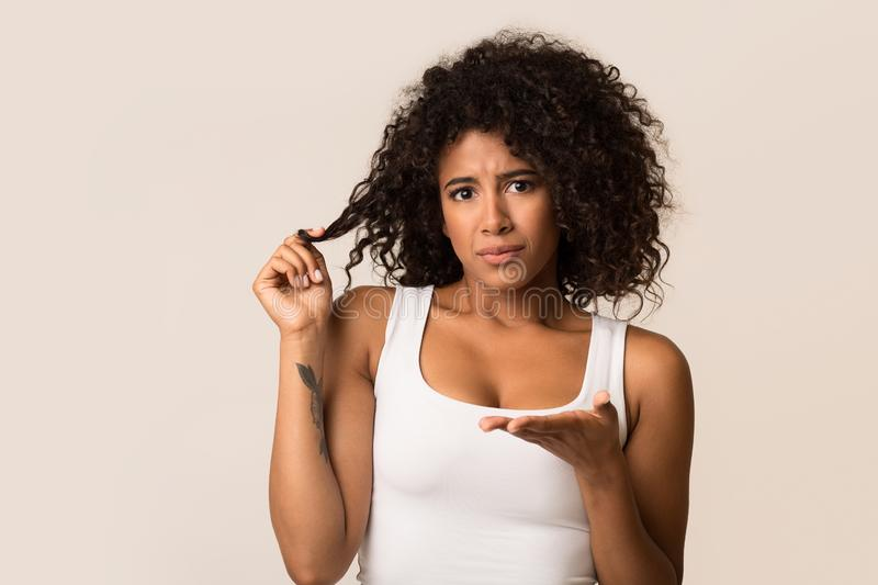 Despaired woman with curly hair on light background stock photos