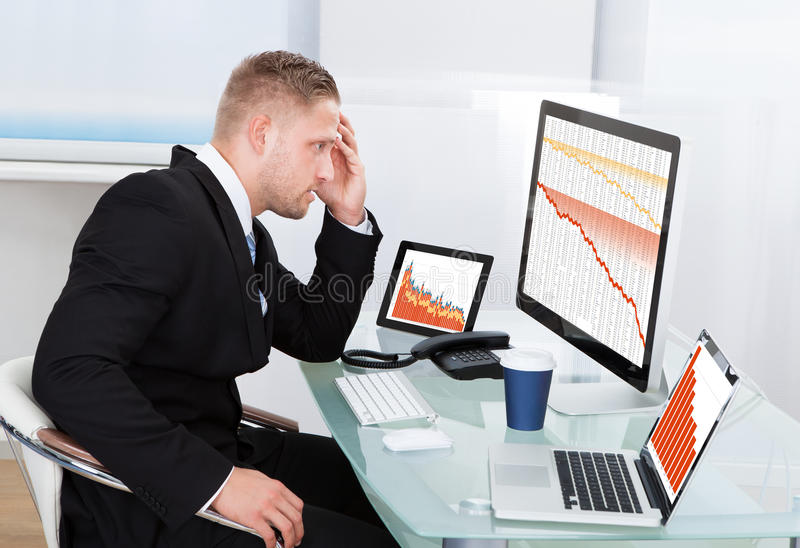 Despairing businessman faced with financial losses. Sitting at his desk consulting three graphs on different monitors all dropping into the red stock photos