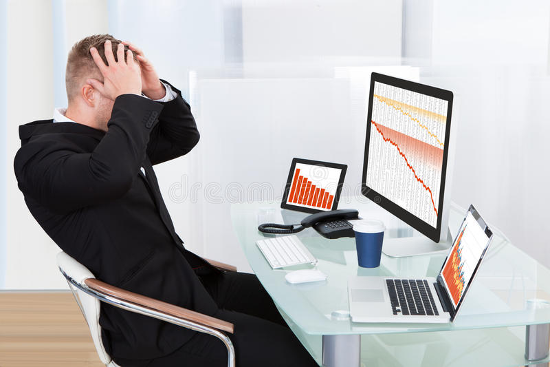 Despairing businessman faced with financial losses. Sitting at his desk consulting three graphs on different monitors all dropping into the red stock photography