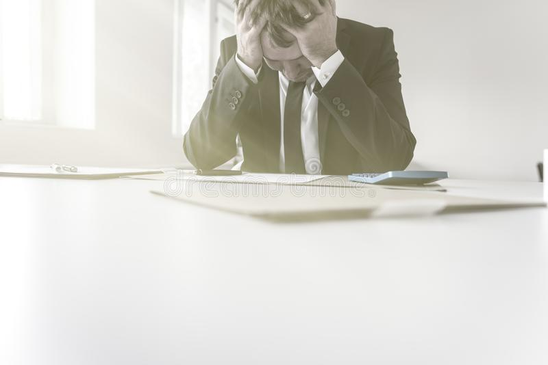 Despairing businessman with his head in his hands. Sitting at his desk with paperwork and a calculator after trying to balance his books royalty free stock photos