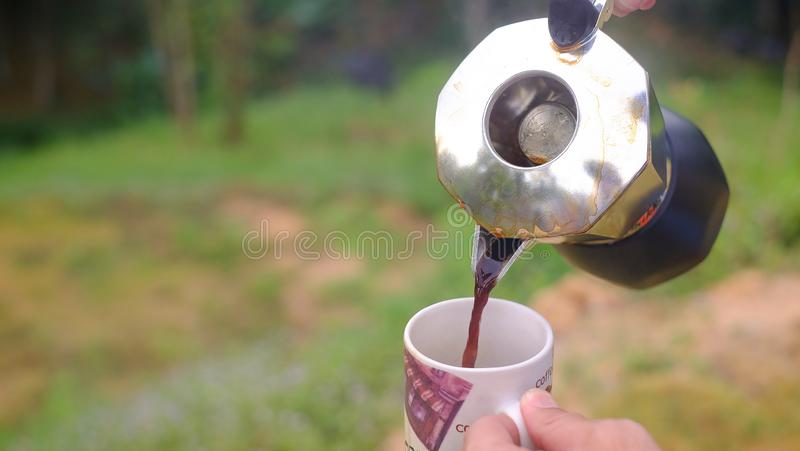 Despejando uma xícara de café quente no vidro para fundo natural quebradiço imagens de stock royalty free