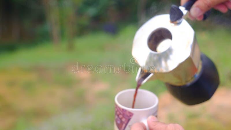 Despejando uma xícara de café quente no vidro para fundo natural quebradiço imagem de stock