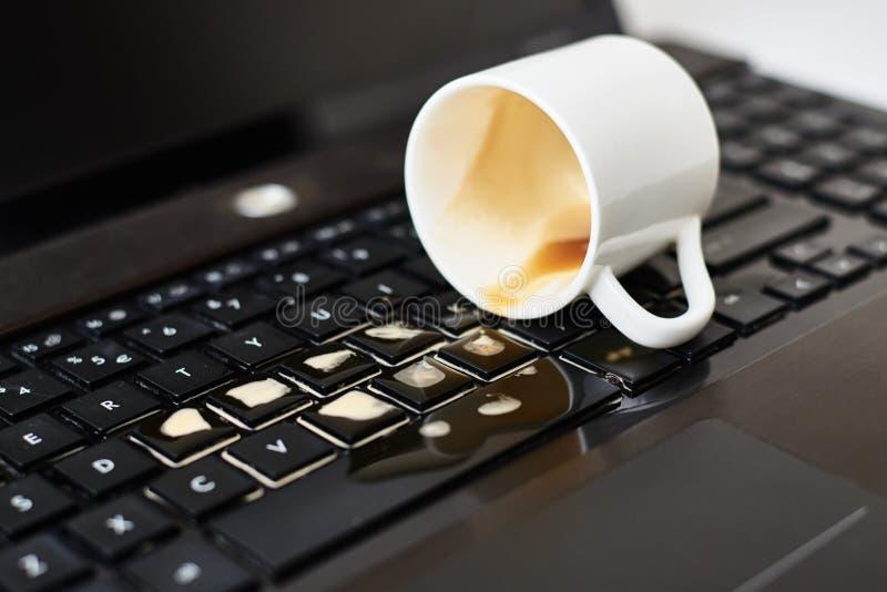 Despeje café da xícara branca no teclado do notebook Danos causados ao computador por derramamento de líquido fotos de stock