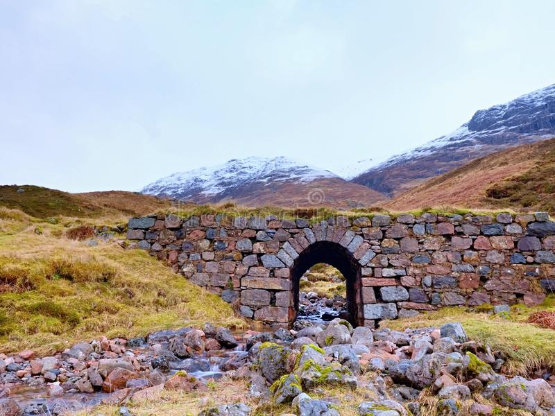 Despeje el río curvado de la corriente debajo del puente pedregoso viejo Trayectoria de las ovejas de montaña fotografía de archivo libre de regalías