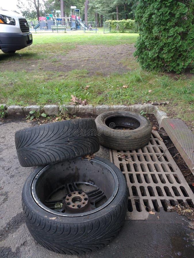 Despejo ilegal, pneus perto de um dreno da tempestade imagens de stock
