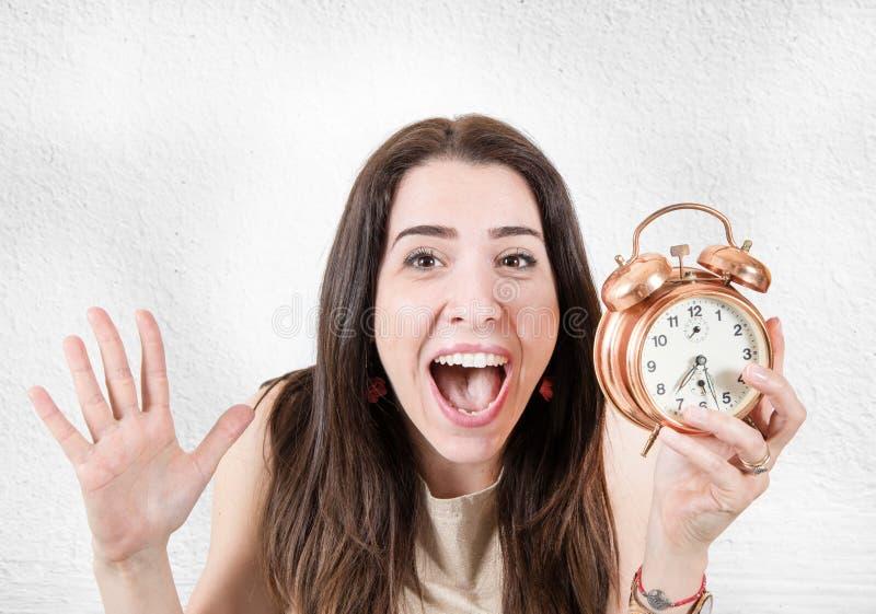 Desperacka kobieta z alarmem ponieważ póżno zdjęcia stock