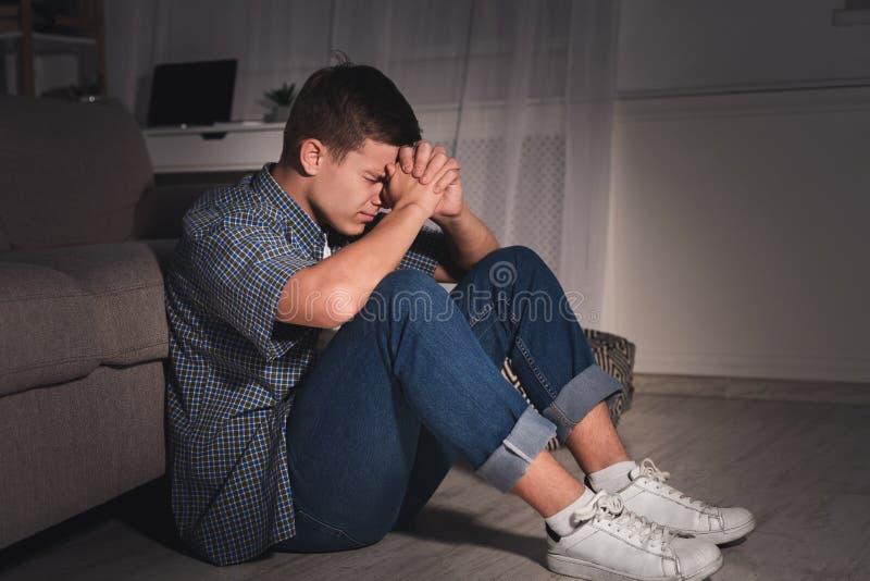 Desperacka nastoletnia chłopiec w ciemnym pokoju w domu zdjęcia royalty free