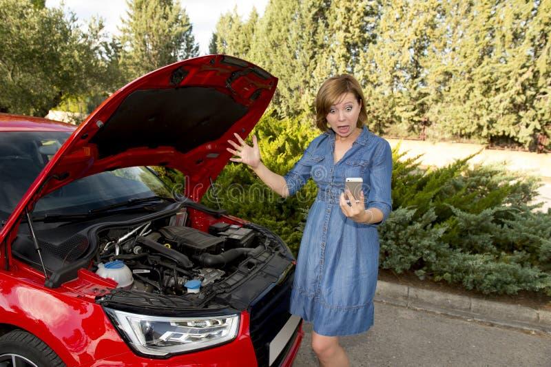 Desperacka zmieszana kobieta dzwoni na telefonie komórkowym splatał z łamanym samochodowego silnika trzaska wypadkiem fotografia royalty free