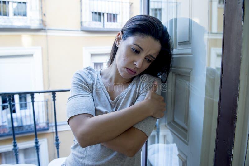 Desperacki Łaciński kobiety balkonowy patrzeć niszczącym i deprymującym cierpi depresją w domu zdjęcia stock