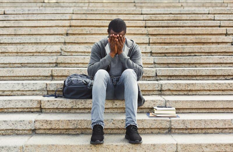 Desperacki afroamerykański studencki obsiadanie na schodkach outdoors zdjęcie royalty free