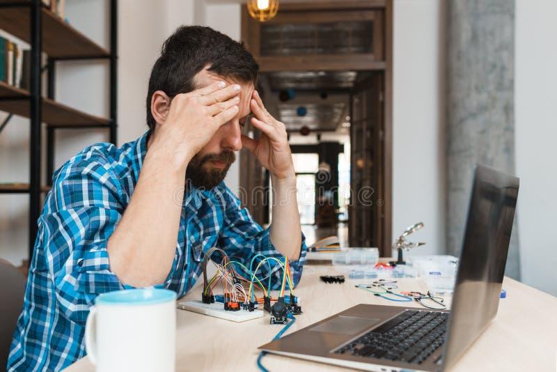 Desperacki inżynier siedzi blisko laptopu zdjęcia stock