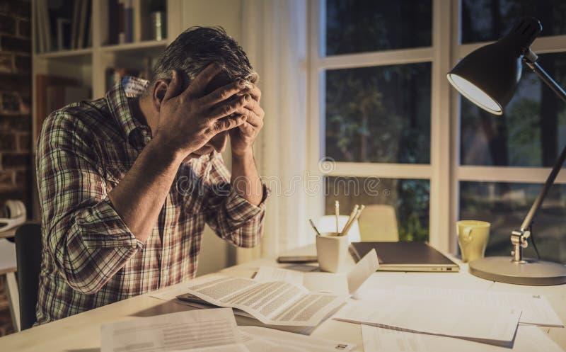 Desperacki mężczyzna sprawdza jego domowych rachunki w domu obraz stock