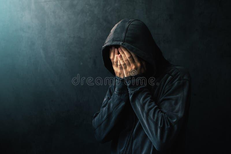 Desperacki mężczyzna w kapturzastej kurtce płacze obrazy stock