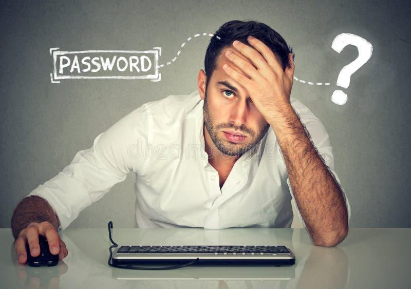 Desperacki młody człowiek próbuje notować w jego komputer zapominał hasło zdjęcie royalty free