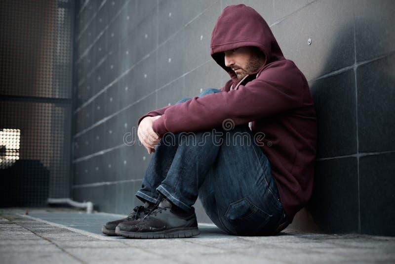 Desperacki osamotniony mężczyzna sadzający przeciw ścianie w mieście obraz royalty free