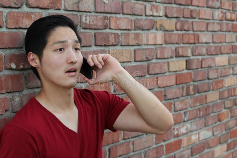 Desperacki smutny przystojny młody Azjatycki mężczyzna słucha zła wiadomość na jego telefonie komórkowym Ludzka emoci reakcja obrazy royalty free