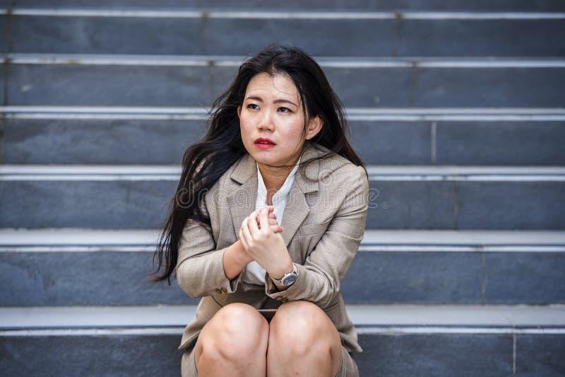 Desperat asiatisk amerikansk affärskvinna som gråter bara att sitta på spänning för gatatrappuppgånglidande och fördjupningskrise fotografering för bildbyråer