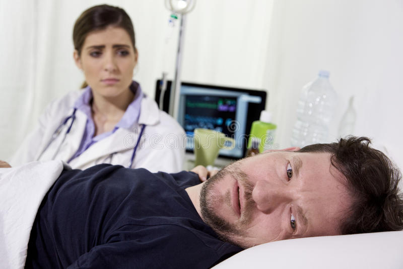 Desperat dåligt man i sjukhussäng som gråter nästan för hans healtvillkor Doktorn sitter bredvid honom arkivfoto