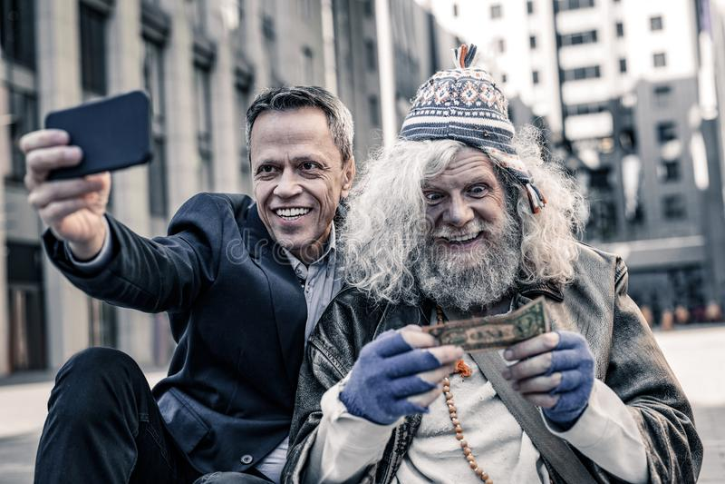 Desperat fattig gamal man som kysser dollarräkningen, medan le mannen som gör fotoet royaltyfria foton