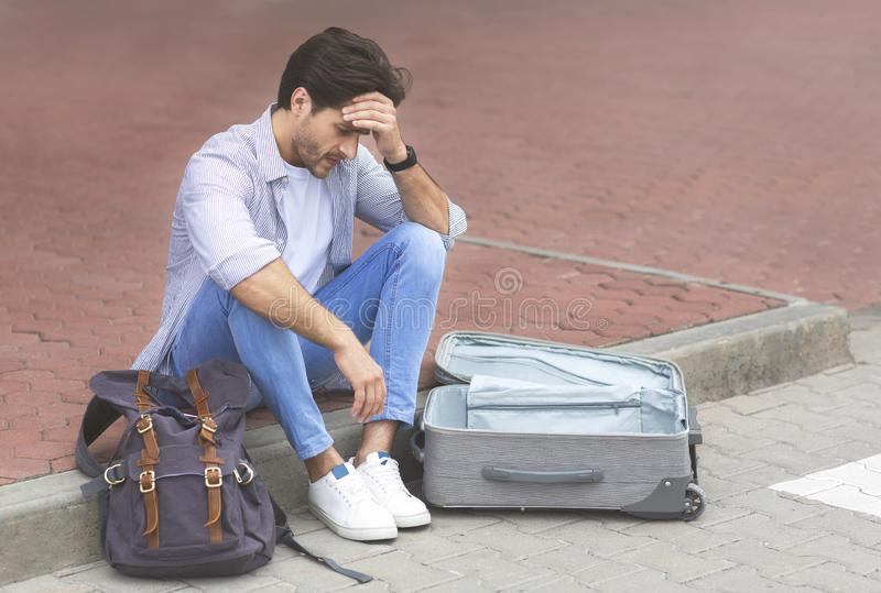 Desperat handelsresande som sitter på den internationella flygplatsen med den tomma resväskan royaltyfria foton