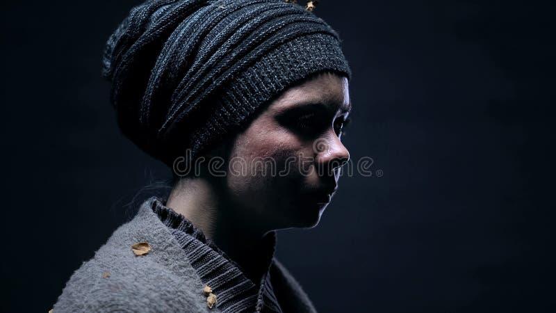 Desperat hemlös kvinnlig på den mörka bakgrundscloseupen, anfall i familj, armod royaltyfri bild