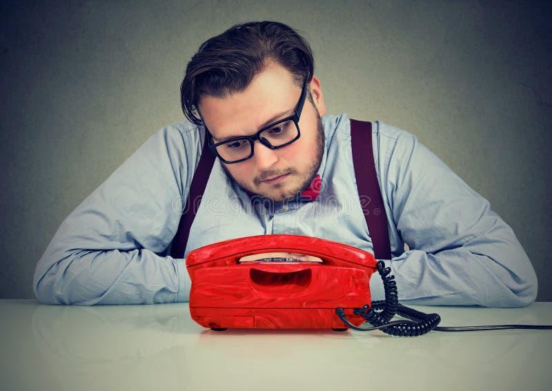 Desperat ledsen man som väntar på någon att kalla honom arkivfoton