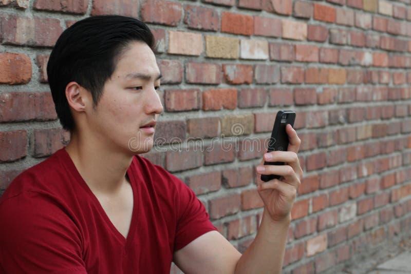 Desperat ledsen stilig ung asiatisk man som ser det dåliga textmeddelandet på hans mobiltelefon Mänsklig sinnesrörelsereaktion arkivbild