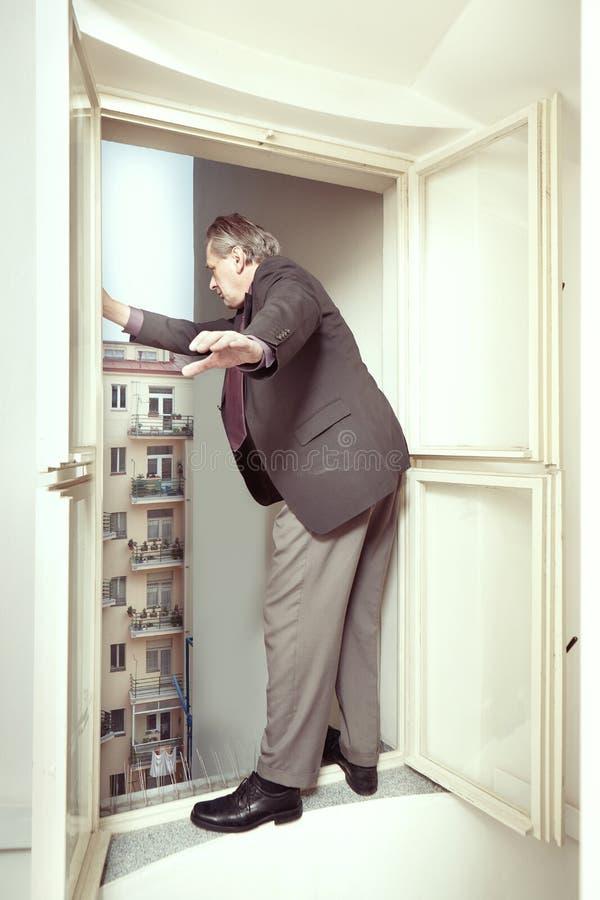 Desperat man som är ledsen av banktrupcyen som tänker av hopp ut ur fönster arkivfoton