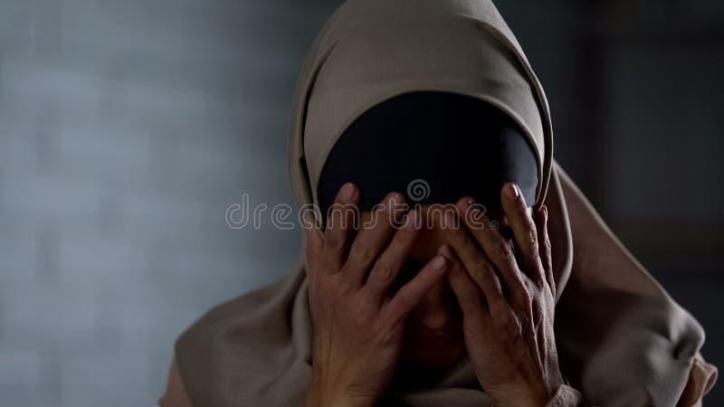 Desperat muslim gr?ta f?r kvinna som t?cker framsidan med h?nder, familjproblem, skam arkivfoto