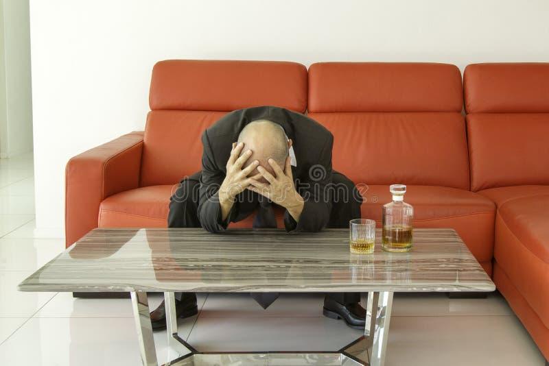 Desperat och deprimerad man med den svarta dräkten som spenderar tid med flaskan av whisky arkivfoto