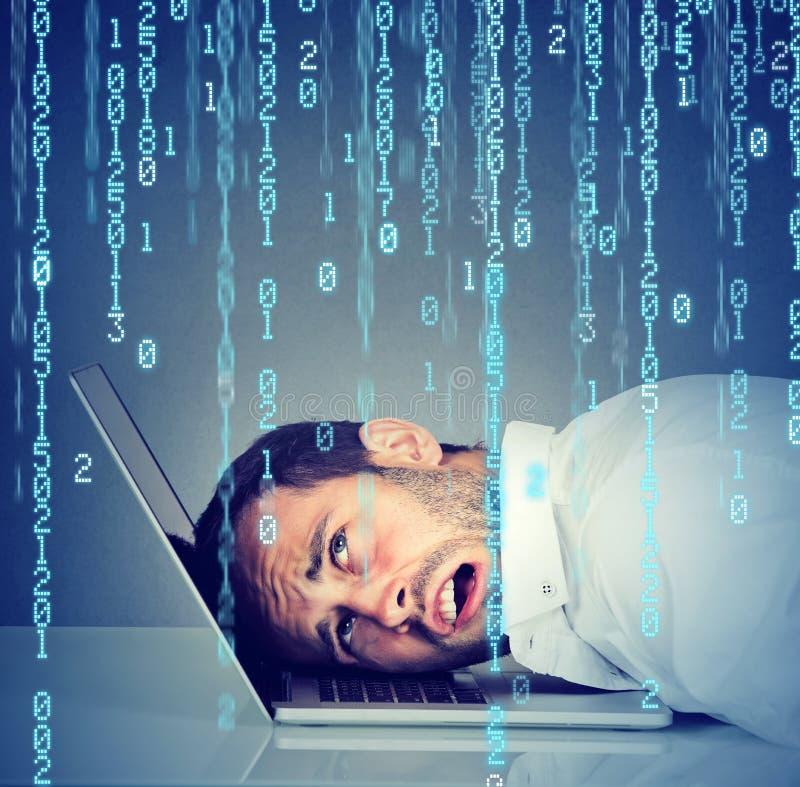 Desperat stressad man som vilar huvudet på bärbara datorn med den binära koden som ner faller arkivbilder