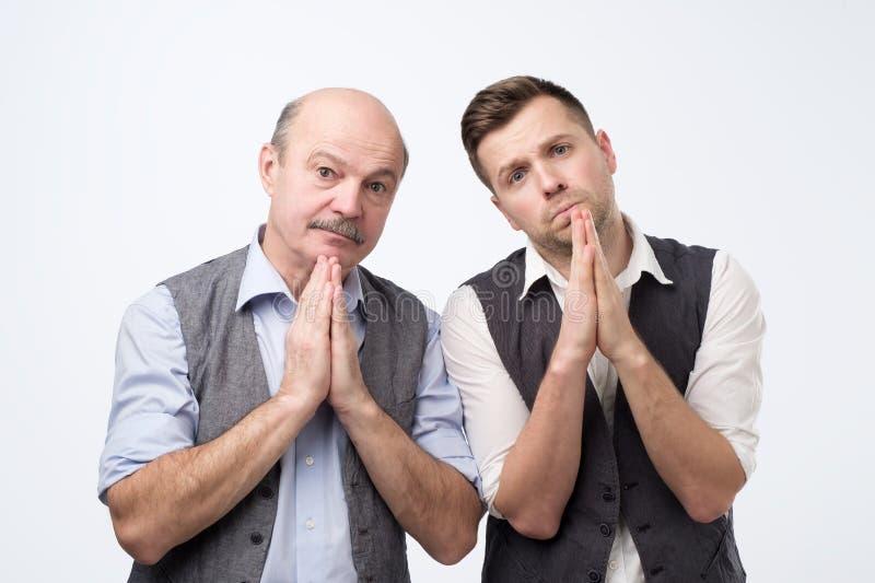 Desperata två män som visar knäppte fast händer som frågar för hjälp royaltyfri fotografi