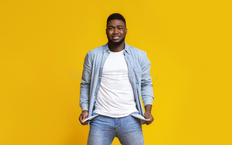 Desperate african american guy showing empty pockets over yellow background. I`m broke. Desperate black man showing empty turned out pockets over yellow studio royalty free stock photo