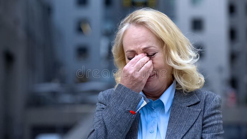Desperate aged woman in business suit crying outdoors office building, dismissal. Stock photo stock image