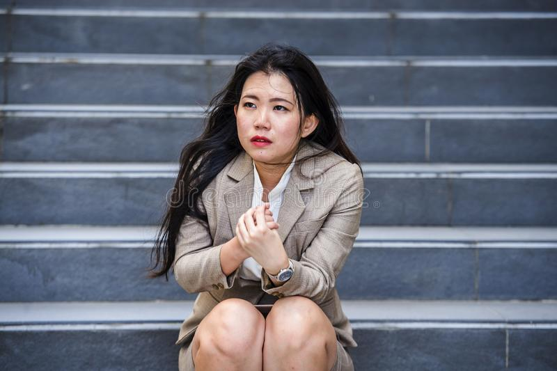 Desperate Asian American business woman crying alone sitting on street staircase suffering stress and depression crisis being stock image