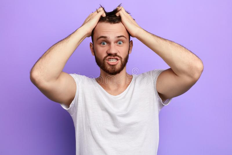 Desperate astonished nervous man tearing his hair. Guy having much problems, cannot solve them. surprised huy with hands on his head looking at the camera, he royalty free stock photo