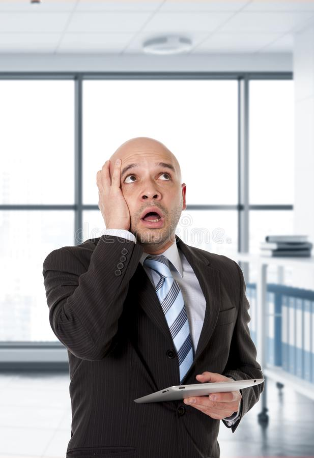 Desperate bald Latin business man in panic face expression holding digital tablet computer royalty free stock images