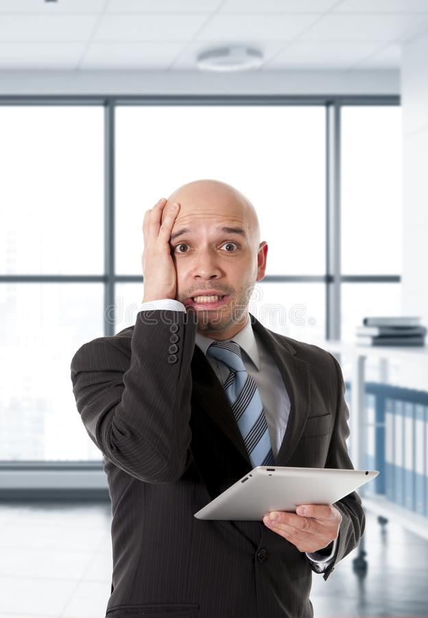 Desperate bald Latin business man in panic face expression holding digital tablet computer stock photography