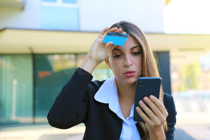Desperate business woman looking on mobile phone her credit card statement stressed. Credit card cloned concept.  royalty free stock photography