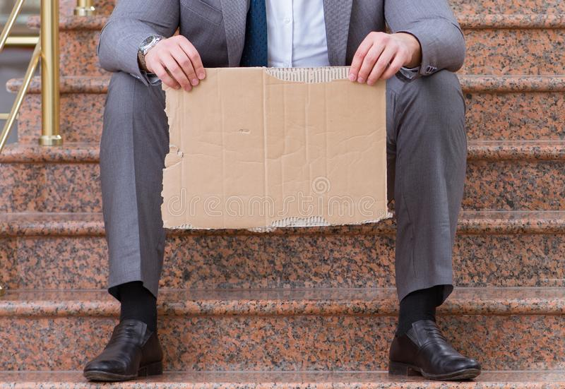 Desperate businessman begging on the street royalty free stock photos