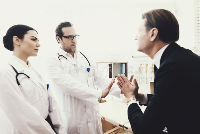 Desperate businessman begs experienced doctor to take money to cure disease. stock photography