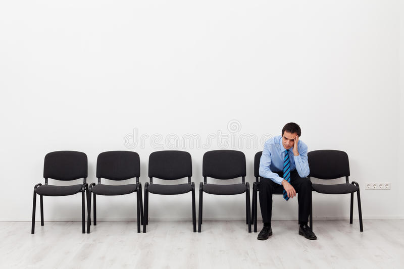Desperate businessman or employee sitting alone. Prompting his head royalty free stock photos