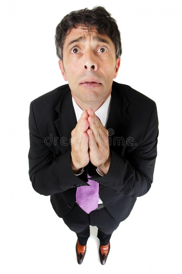 Desperate businessman praying. Humorous high angle full length portrait of an expressive desperate businessman praying in supplication pleading for help isolated royalty free stock image