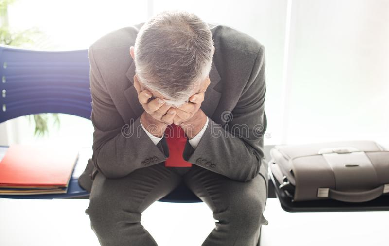 Desperate businessman in the waiting room stock photo