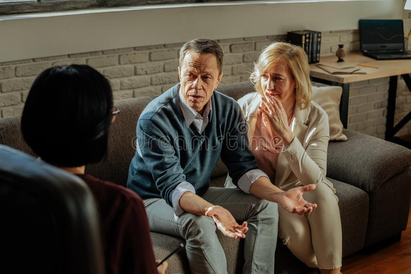Desperate couple having middle-age crises and talking about it. Appointment with family. Desperate couple having middle-age crises and talking about it with dark stock images