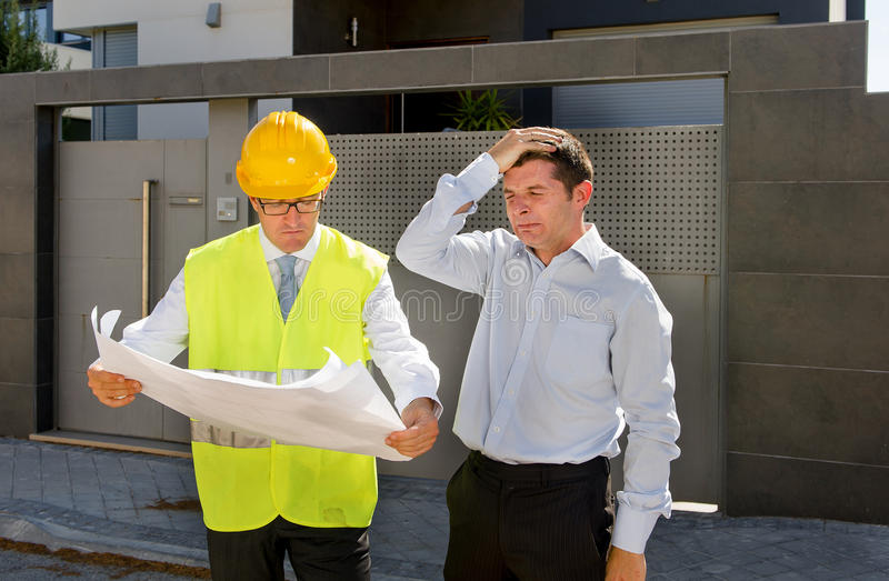 Desperate customer in stress and constructor foreman worker with helmet and vest arguing outdoors on new house building blueprints. Unhappy customer in stress royalty free stock image